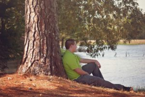 Teenager leaning by tree