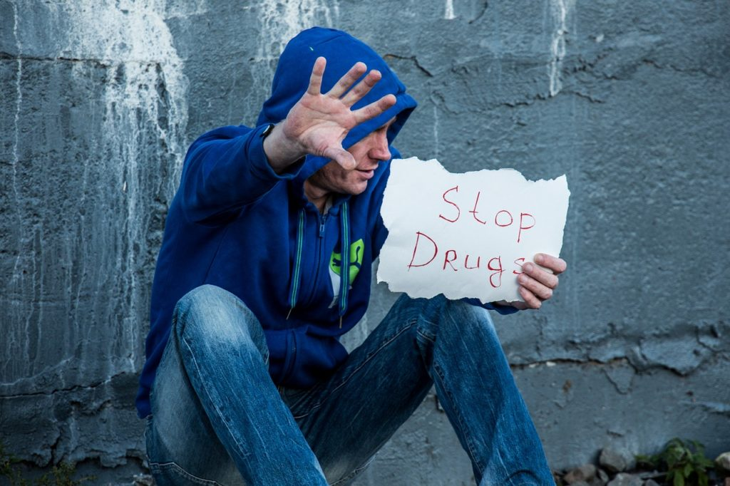 Man holding up a stop drugs sign