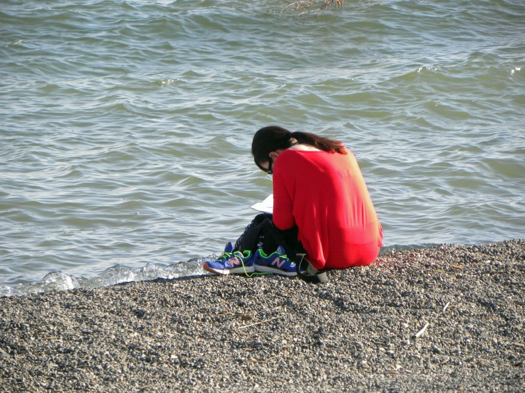 Woman praying on the shore