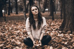 Upset Woman Sitting Outside In Leaves