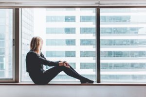 Woman sitting in window sill and thinking about medical stabilization for opiate addiction