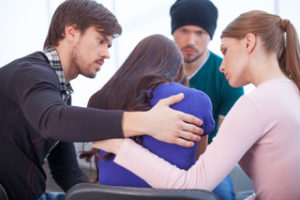 Group of people comforting someone with sexual addiction