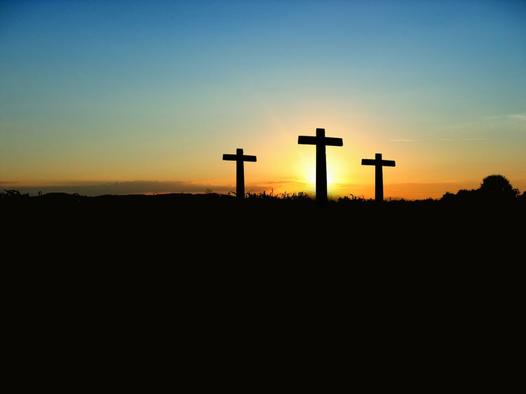 Three crosses with sunset behind it