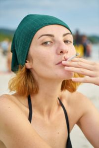 Woman smoking on the beach