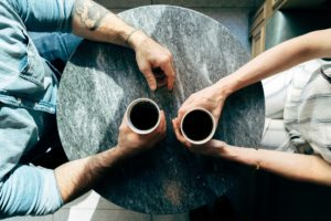 Partners discussing emotionally abusive relationships over coffee
