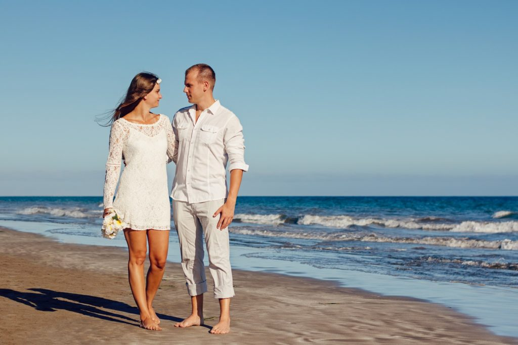 Couple walking on the beach after being married
