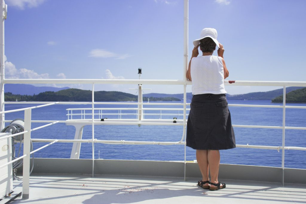 Older Woman standing on a deck of a ship contemplating Alcohol Use Disorders in Older Women