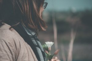 Woman holding flower and thinking about opioid overdose