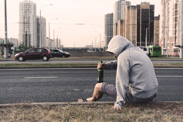 Man sitting on a curb with a beer in his hand