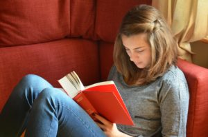 Teen girl reading about summer addiction treatment