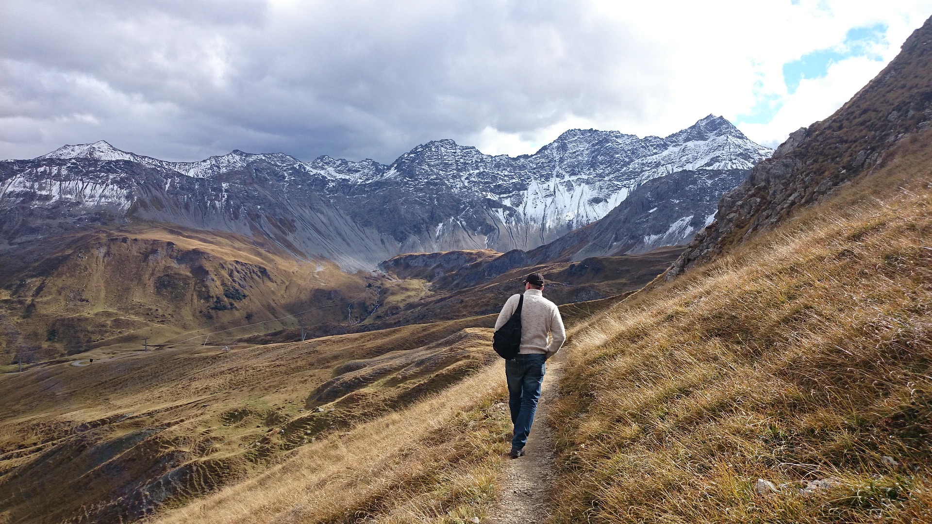 Man walking a trail in the mountains