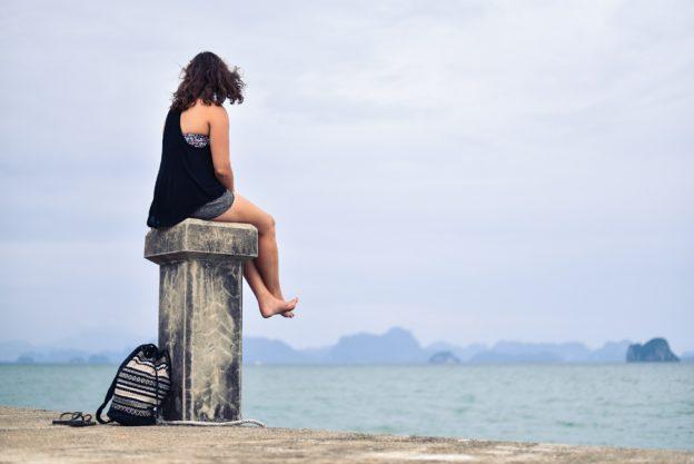 Woman sitting on pillar at the beach