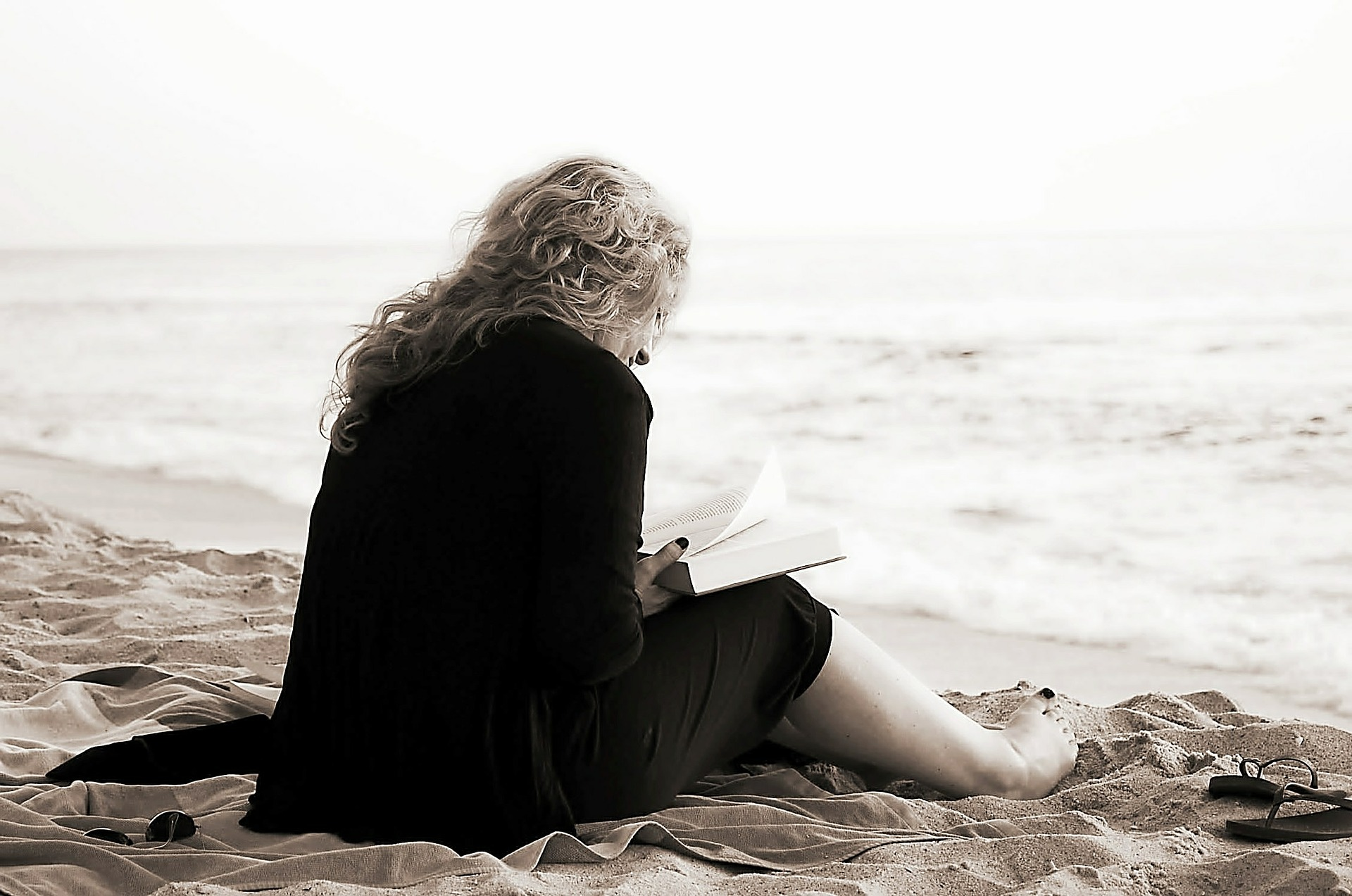 Lady sitting on the beach reading a book
