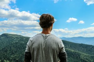 Guy in mountains thinking about Substance Use Disorder Recovery