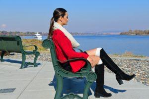 Hispanic Woman Sitting on Bench Near Sea